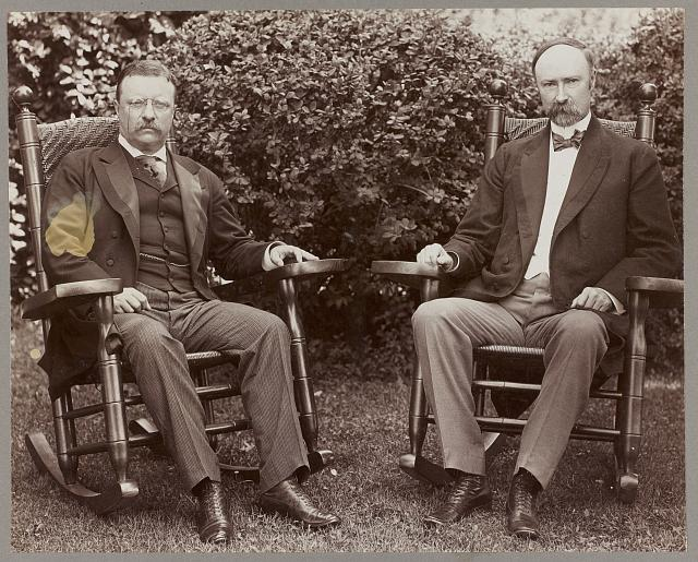 [President Theodore Roosevelt and Vice President Charles Fairbanks, seated in rocking chairs on a lawn]