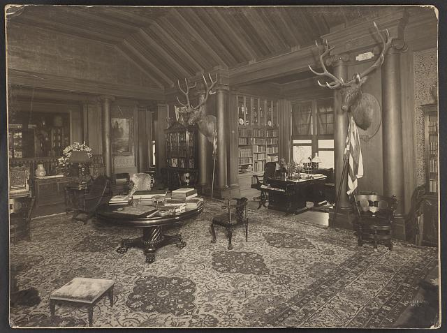 [Library(?) at Theodore Roosevelt's home, Sagamore Hill, Long Island, with two elk heads on wall]