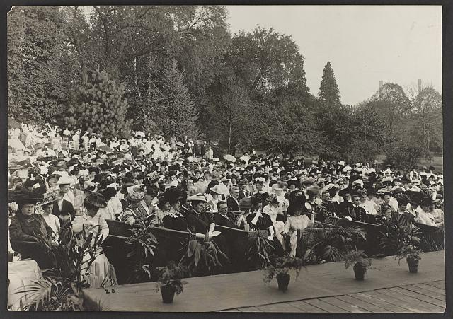 [Teddy Roosevelt seated in an outdoor stage box, surrounded by other audience members]