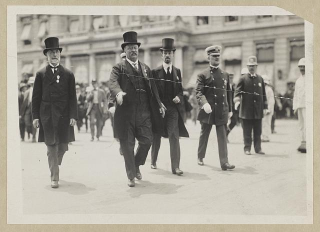 [Theodore Roosevelt between Mayor Gaynor and Cornelius Vanderbilt, with hand outstretched to greet Rough Rider, New York City parade]