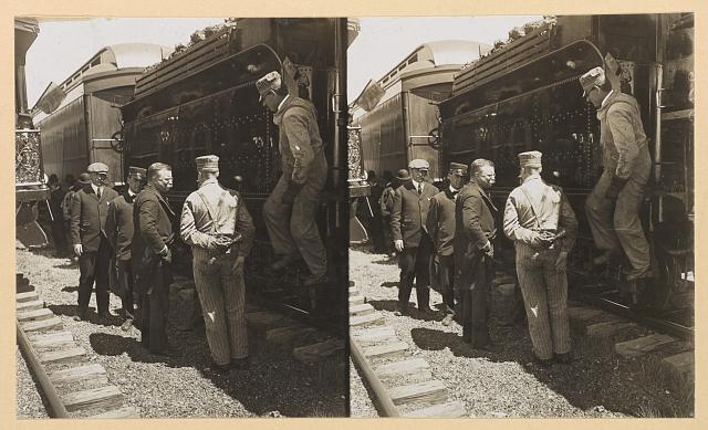 [Theodore Roosevelt standing by a railroad car with workers and other men]