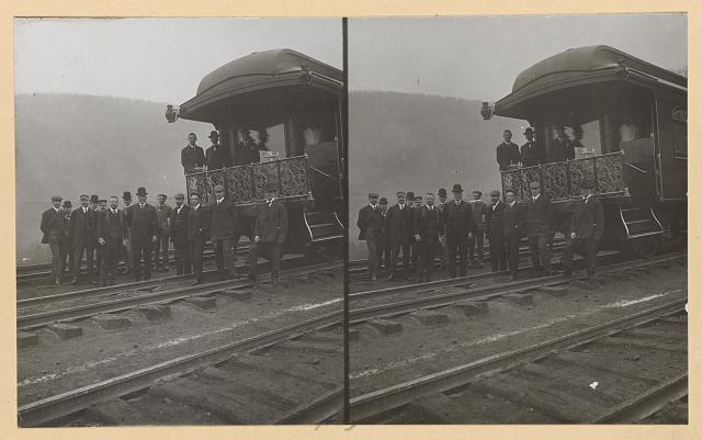 [President Roosevelt, standing with twelve other men on railroad tracks, in front of locomotive]