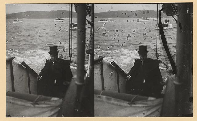 [Theodore Roosevelt wearing a tall hat and cape climbs up the steps aboard a ship]