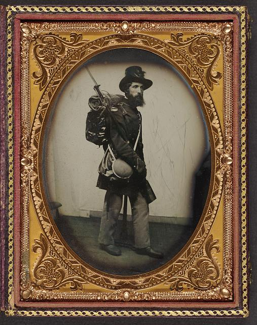 [Private Albert H. Davis of Company K, 6th New Hampshire Infantry Regiment in uniform, shoulder scales, and Hardee hat with Model 1841 Mississippi rifle, sword bayonet, knapsack with bedroll, canteen, and haversack]