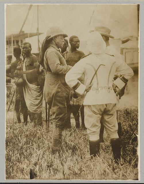 [Theodore Roosevelt standing with mostly African men in traditional dress]