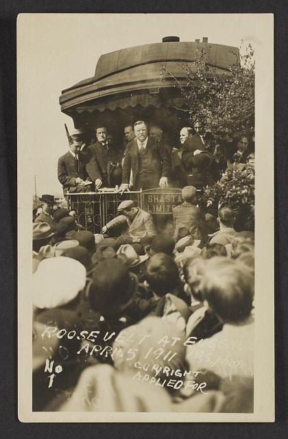 [Theodore Roosevelt with others standing on back of train, facing crowd. Eugene, Ore. April 5, 1911]