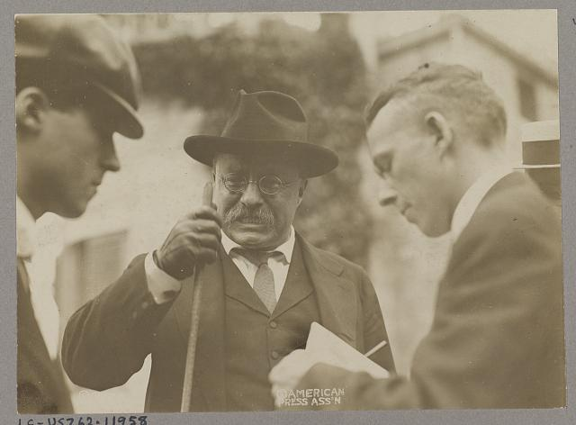[Theodore Roosevelt speaking with two men, probably reporters]