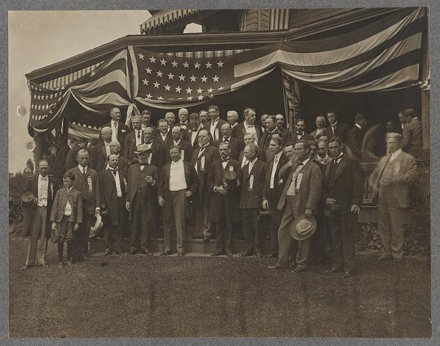 [Theodore Roosevelt standing in center of a group of men outside a porch draped with American flags]