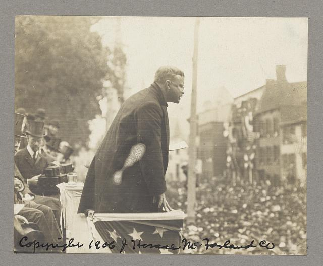 [President Theodore Roosevelt addressing a crowd from a flag-draped podium]