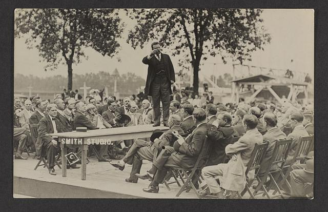 [Theodore Roosevelt standing on a table speaking to a seated audience]