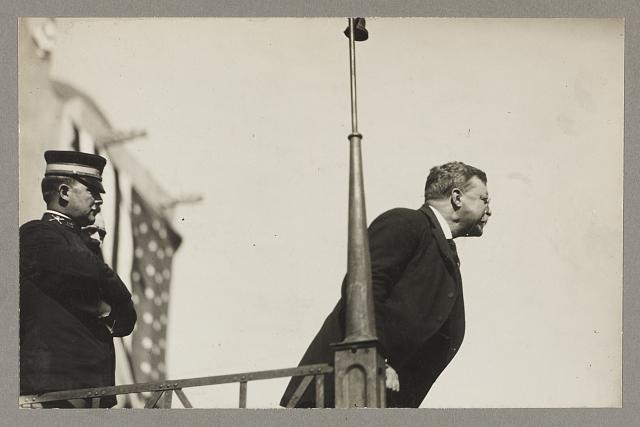 [Theodore Roosevelt speaking on a raised platform, leaning forward toward the audience]
