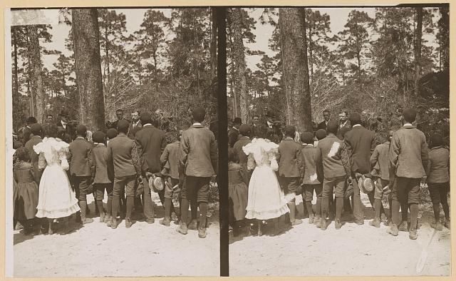 [Theodore Roosevelt speaking to a group of African American children on the edge of woods]