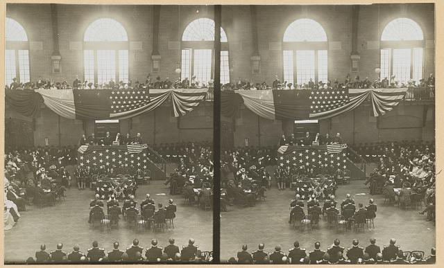 [Teddy Roosevelt on a flag-draped platform, speaking to a group of people]