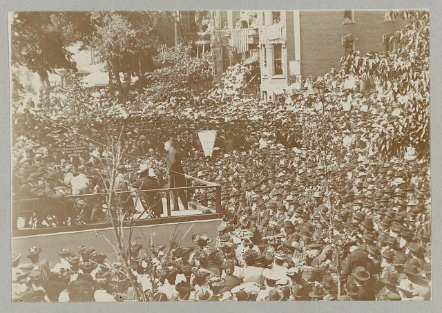 [Theodore Roosevelt on a platform speaking to a large group, possibly veterans]