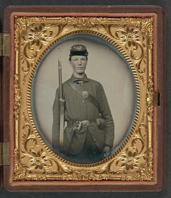 [Corporal Alvin B. Williams of Company F, 11th Regiment New Hampshire Volunteers, with musket and a bayonet in scabbard; dog tag in case]