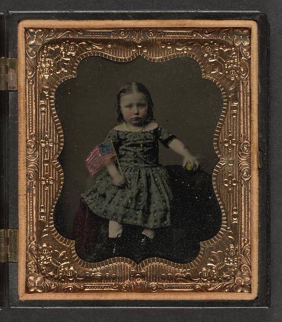 [Unidentified girl in dress holding American flag and ball]