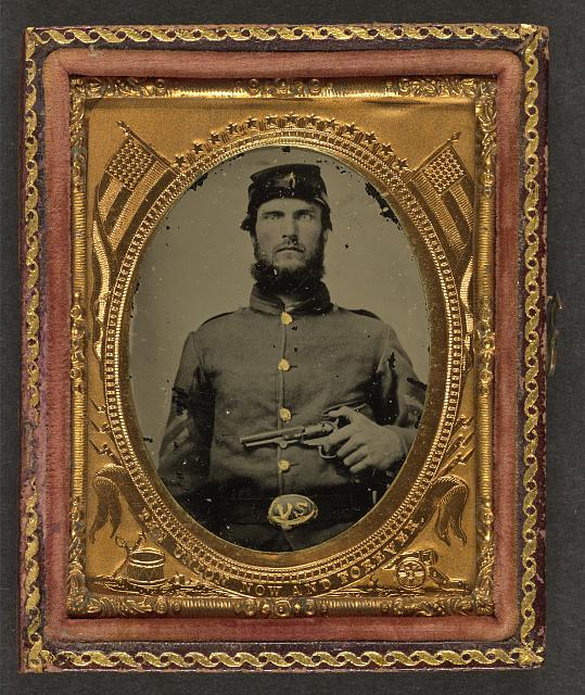 [Unidentified soldier in Union corporal's uniform holding revolver to chest]