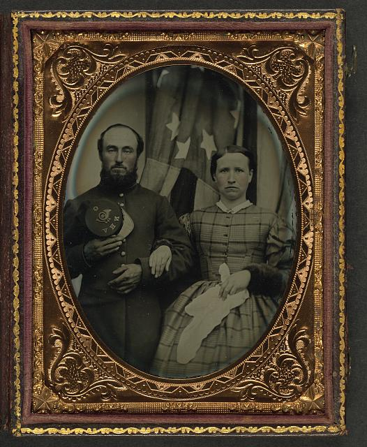 [Unidentified soldier in Union frock coat holding Company G, 12th New Hampshire Infantry Regiment forage cap next to unidentified woman in front of an American flag]