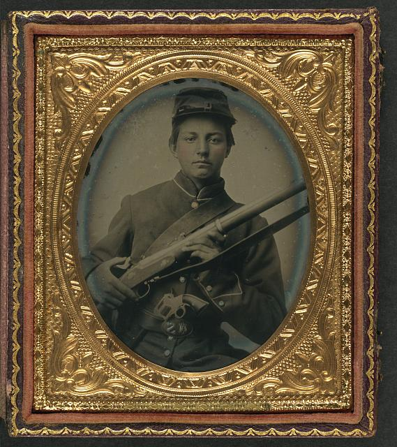[Unidentified young soldier in Union uniform holding musket with Prescott revolver in belt]