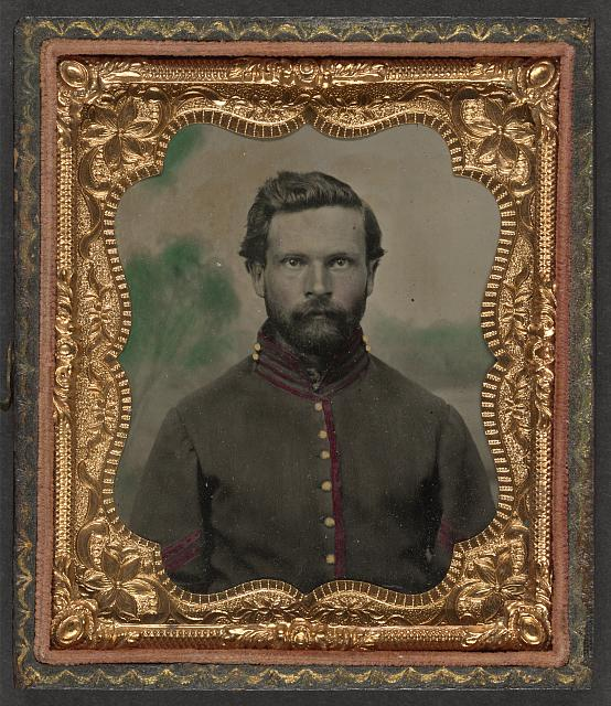 [Unidentified soldier in Union artillery corporal's uniform in front of painted backdrop showing a forest]