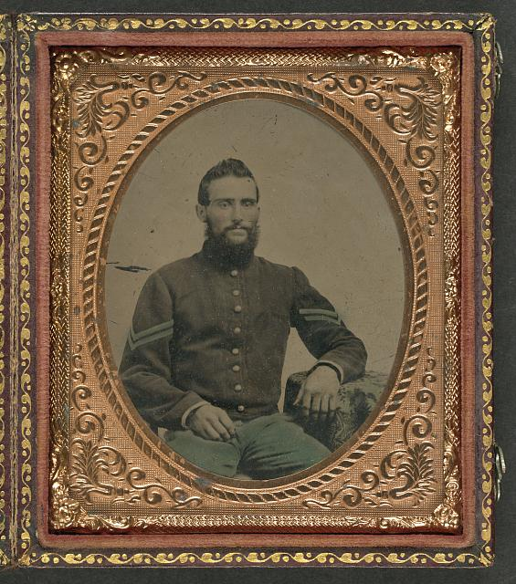 [Unidentified soldier in Union infantry corporal's uniform sitting with arm resting on table]