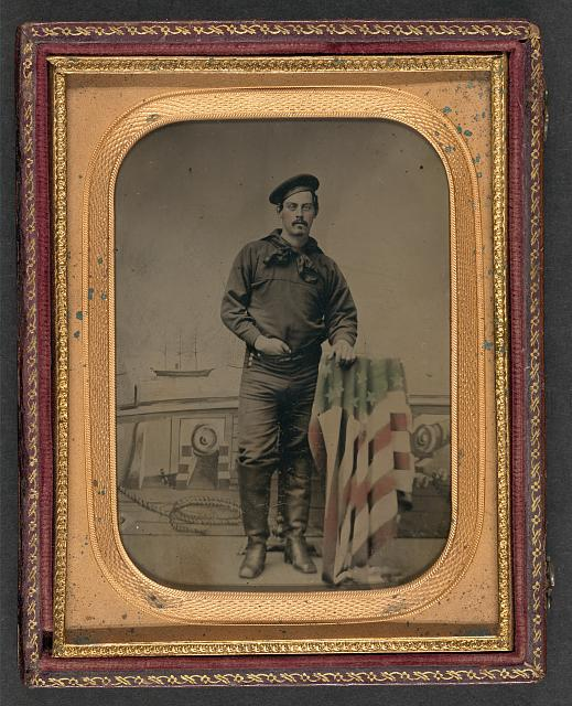 [Unidentified sailor in Union uniform resting hand on American flag-draped table in front of painted backdrop showing naval scene]