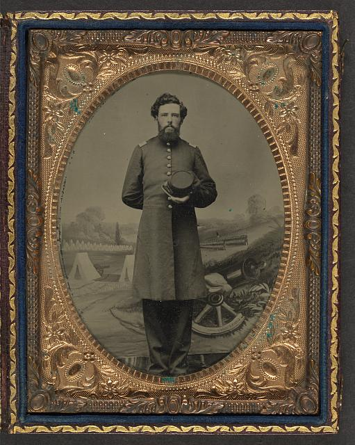 [Unidentified soldier in Union frock coat with hat in front of painted backdrop showing military camp scene]