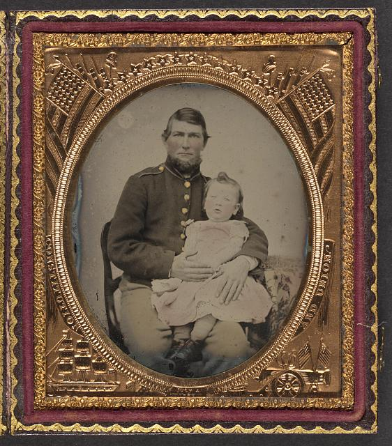 [Unidentified soldier in Union uniform holding a young child in his lap]