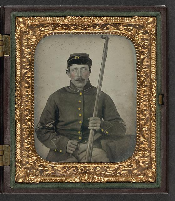 [Unidentified soldier in Union corporal's uniform and forage cap sitting with bayoneted musket]