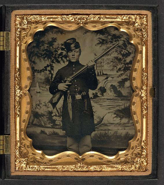 [Unidentified soldier of the 2nd United States Sharpshooters in Union uniform with target rifle, bowie knife, and Colt '49 pocket revolver in front of painted backdrop showing landscape with lake and fort]