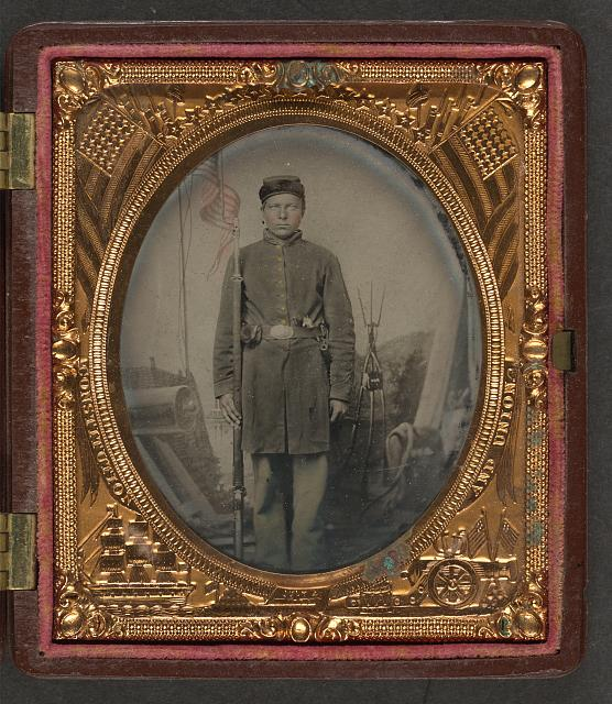 [Unidentified soldier in Union uniform with musket, bayonet in scabbard, revolver, and cap box in front of painted backdrop showing military camp scene]