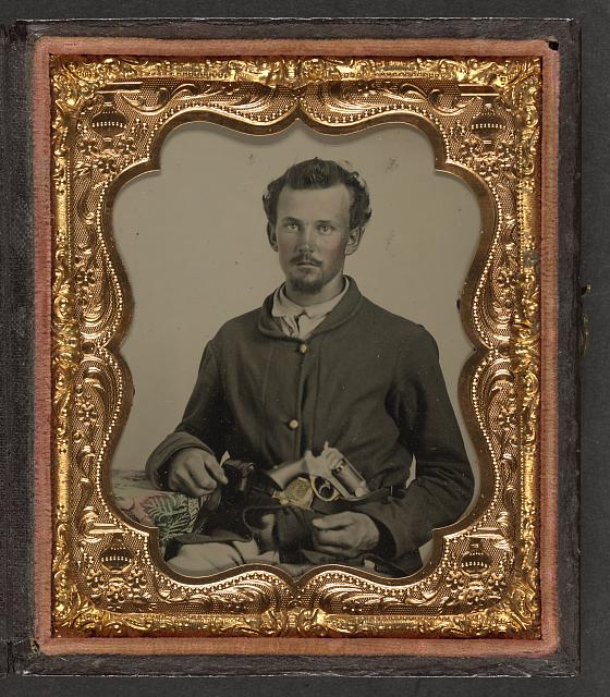 [Unidentified soldier in Union uniform with revolver in belt resting his arm on a table]