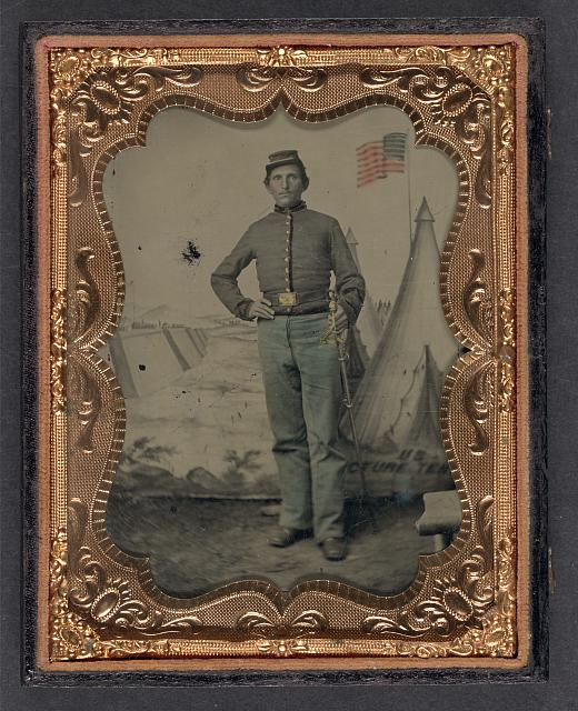 [Unidentified soldier in Union uniform with cavalry saber in front of U.S. Picture Tent painted backdrop]