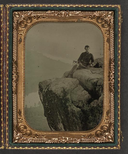 [Unidentified soldier in Union officer's uniform at Point Lookout, Tennessee, sitting with cavalry saber in hand and slouch hat resting beside him on a rock]