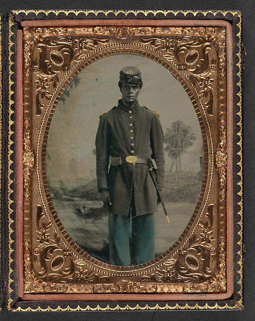 [Unidentified African American soldier in Union uniform and Company B, 103rd Regiment forage cap with bayonet and scabbard in front of painted backdrop showing landscape with river]