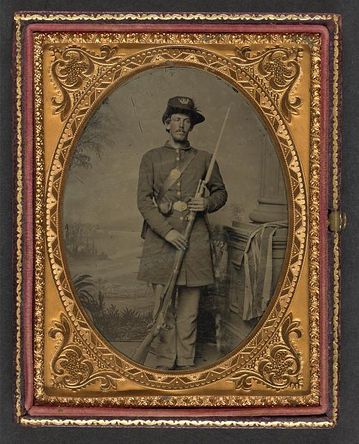 [Unidentified soldier in Union uniform and plumed infantry Company A Hardee hat with bayoneted musket, cap box, and cartridge box in front of painted backdrop showing landscape]