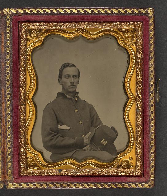 [Unidentified soldier in 1st Michigan Regiment of Engineers and Mechanics private's uniform holding Hardee hat with castle insignia]