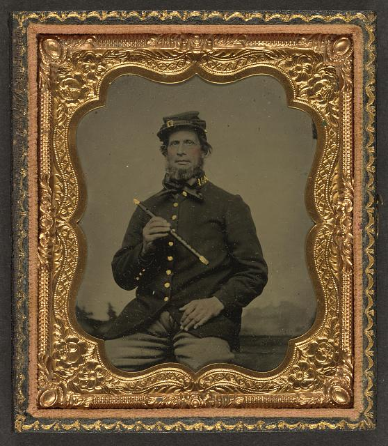 [Unidentified soldier in Union uniform with fife in front of painted backdrop showing a pastoral landscape]