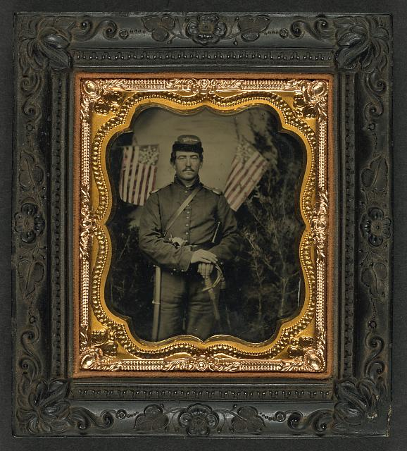 [Unidentified soldier in Union uniform with shoulder scales with pearl-handled revolver and saber in front of backdrop showing trees and two Great Star flags]
