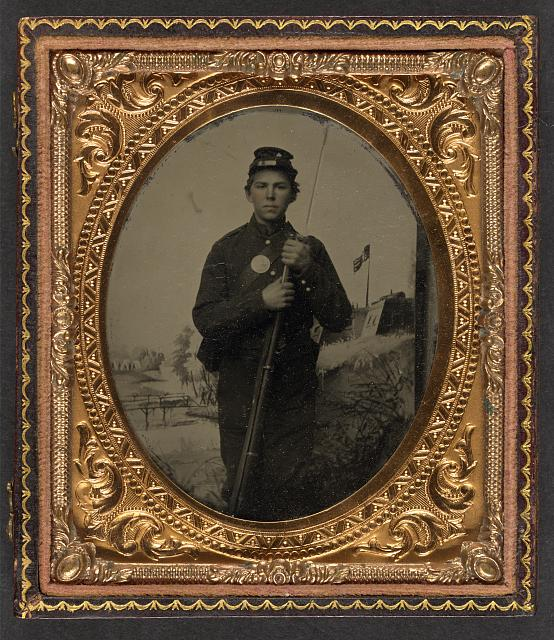 [Unidentified young soldier in Union uniform with musket in front of painted backdrop showing fort]