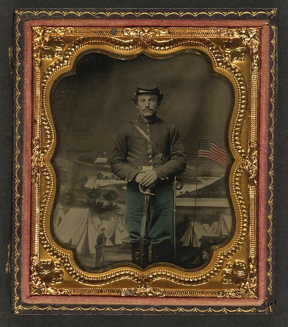 [Unidentified soldier in Union uniform with sword in front of painted backdrop showing military camp scene]
