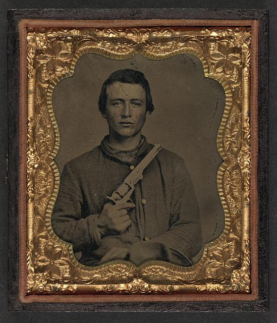 [Unidentified soldier in Union uniform holding Colt revolver to chest]