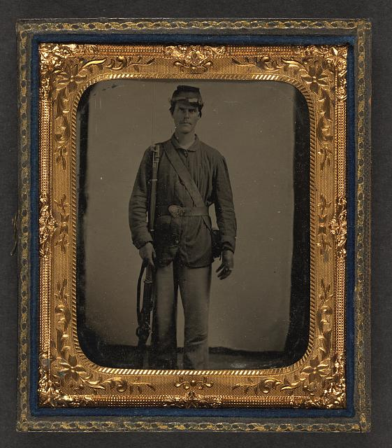 [Unidentified soldier in Union uniform with bayoneted musket and cartridge box in front of canvas backdrop]