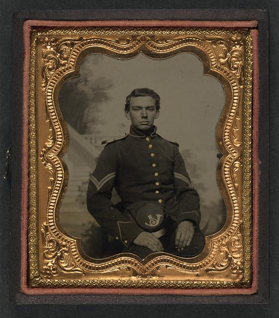 [Unidentified soldier in Union corporal&#39;s uniform with 1858 Army hat of Company H, 4th Infantry Regiment in front of painted backdrop showing outdoor scene]