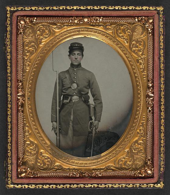 [Unidentified young soldier in Union uniform and cap and cartridge box with bayoneted musket, bayonet and scabbard, and sword]