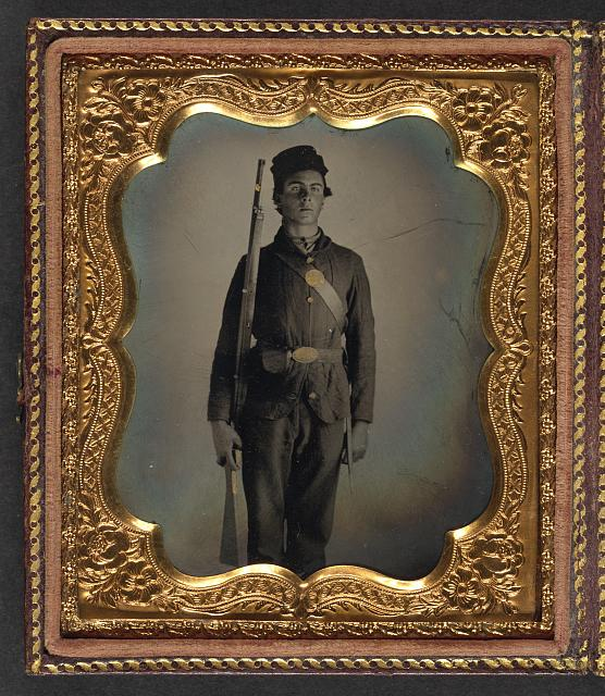 [Unidentified soldier in Union uniform and cap box standing with musket and bayonet with scabbard]