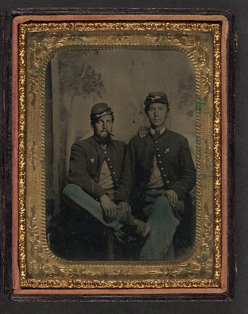 [Two unidentified soldiers in Union uniforms in front of painted backdrop showing trees]