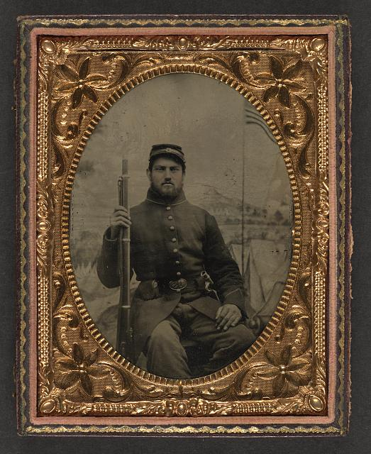 [Unidentified soldier in Union frock coat and kepi holding musket in front of painted backdrop showing military camp]