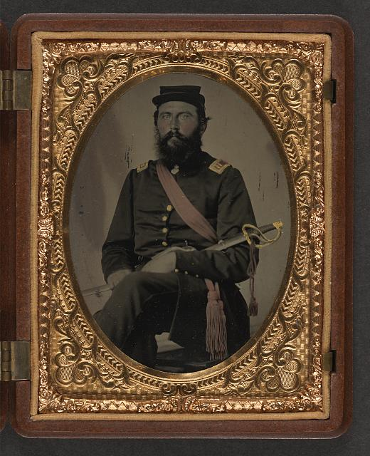 [Unidentified soldier in Union Captain uniform with crimson sash holding cavalry saber]