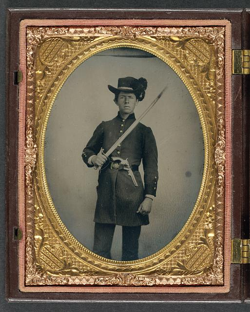 [Unidentified young soldier in Confederate uniform and Hardee hat with holstered revolver and artillery saber]